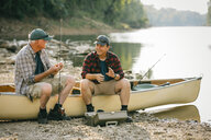 Male friends with fishing rods talking while sitting on boat at lakeshore - CAVF59019