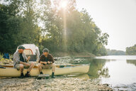 Friends with fishing rods talking while sitting on boat at campsite - CAVF59022