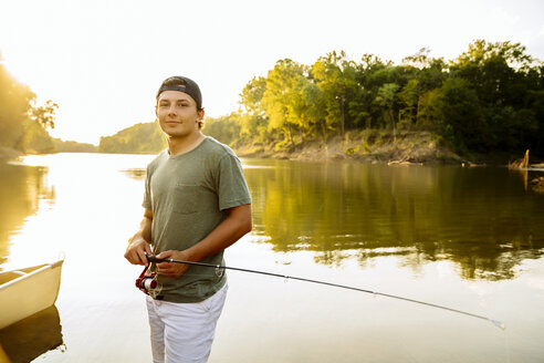 Portrait of young man with fishing rod standing at lakeshore against clear sky during sunset - CAVF59043