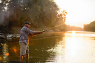 Side view of senior man fishing while standing in lake during sunset - CAVF59055