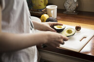 Midsection of woman cutting avocado at kitchen - CAVF59076