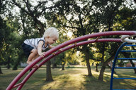 Side view of baby boy climbing monkey bars at park - CAVF59133