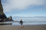 Rear view of boy holding stick while walking on sand at beach against sky - CAVF59145