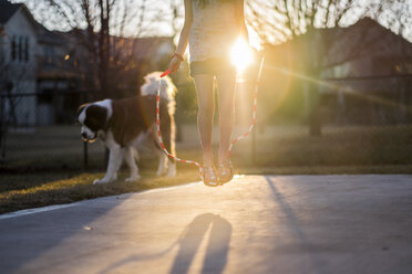Low section of girl jumping rope at playground with dog in background - CAVF59166