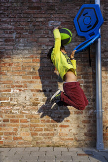Side view of boy playing basketball by brick wall - CAVF59208
