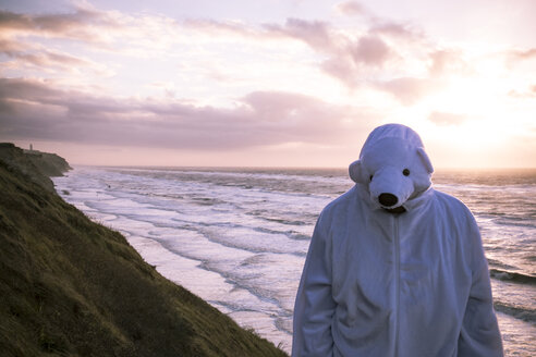 Denmark, Nordjuetland, Man wearing ice bear costume at the beach - REAF00472