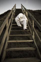 Man wearing ice bear costume sitting on steps, despair - REAF00475