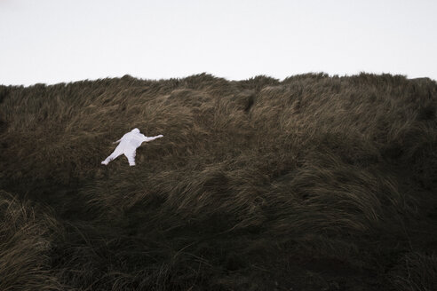 Denmark, Nordjuetland, Man wearing ice bear costume lying in grass - REAF00478