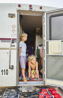 Two smiling boys looking out of door of a camper - SSCF00080