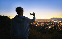 Chile, Santiago, woman taking cell phone picture in the mountains above the city at sunset - SSCF00089