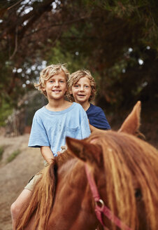 Portrait of two happy boys on horse in a forest - SSCF00092