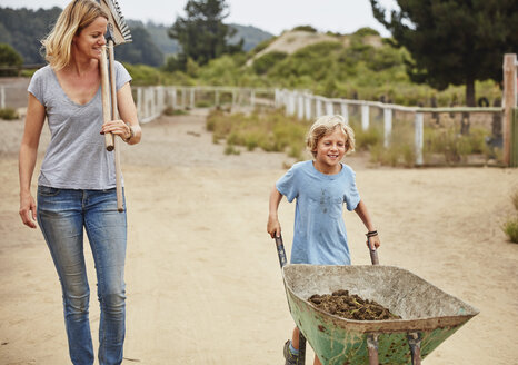 Mother and son pushing wheelbarrow with horse dung - SSCF00095
