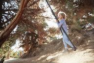 Boy swinging on a rope in backlight - SSCF00110
