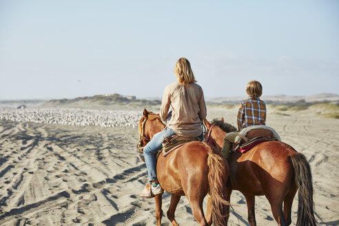 Chile, Vina del Mar, mother with son riding horses on the beach - SSCF00113