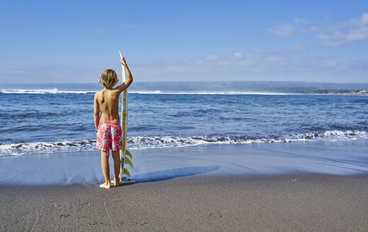 Chile, Pichilemu, boy standing at the sea with surfboard - SSCF00119