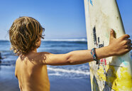 Chile, Pichilemu, boy standing at the sea with surfboard - SSCF00122