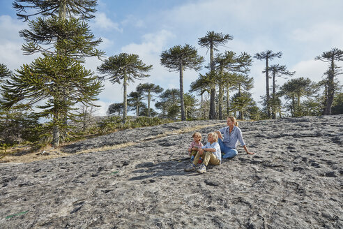 Chile, Puren, Nahuelbuta National Park, woman sitting with sons on boulder in Araucaria forest - SSCF00149