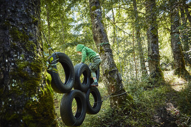 Boy balancing on tyres at an adventure park in forest - SSCF00155