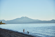Chile, Lago Llanquihue, Calbuco volcano, two boys playing in water - SSCF00164