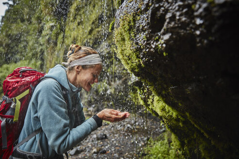 Chile, Patagonia, Osorno Volcano, woman refreshing with water from Las Cascadas waterfall - SSCF00176
