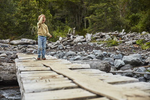 Chile, Patagonia, Osorno Volcano, Las Cascadas waterfall, happy boy on boardwalk above a river - SSCF00179