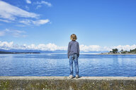 Chile, Puerto Montt, boy standing on quay wall at the harbor - SSCF00182