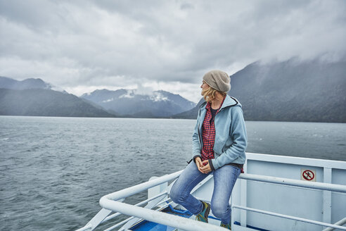 Chile, Hornopiren, woman sitting on rail of a ferry looking at fjord - SSCF00194