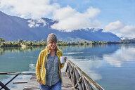 Chile, Chaiten, Lago Rosselot, woman walking on jetty holding mug - SSCF00218