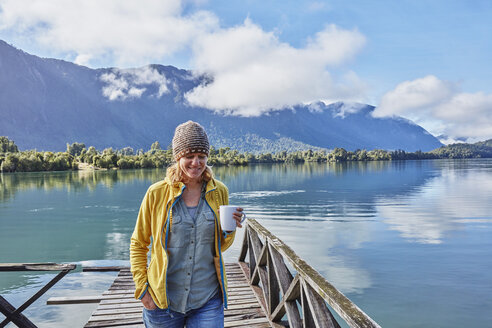 Chile, Chaiten, Lago Rosselot, woman walking on jetty holding mug - SSCF00218