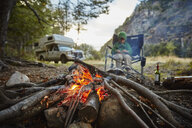 Chile, Santa Magda, Rio Maniguales, boy sitting at campfire in forest with camper van in background - SSCF00224