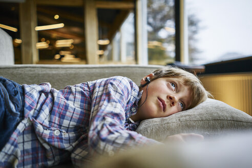 Boy lying on couch with earphones - SSCF00257