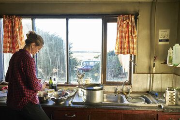 Woman standing in kitchen preparing meal - SSCF00263