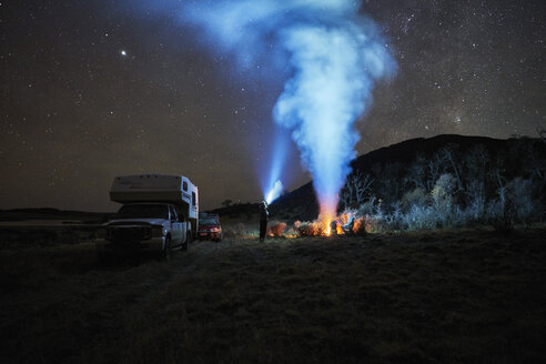 Chile, Tierra del Fuego, Lago Blanco, campfire and people at camper under starry sky at night - SSCF00272