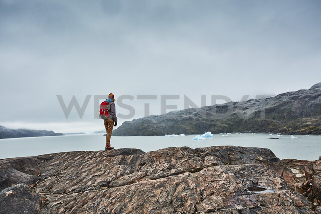 Chile, Torres del Paine National park, Lago Grey, woman standing on rock at the shore looking at iceberg - SSCF00278 - Stefan Schütz/Westend61