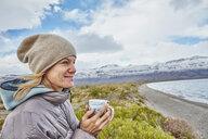 Argentina, Lago Posadas, woman holding mug at lakeside - SSCF00293