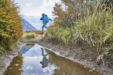 Argentina, Patagonia, El Chalten, boy running at puddle in Los Glaciares National park - SSCF00305