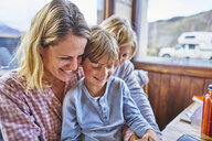 Happy mother with two sons sitting at table in a cafe - SSCF00317