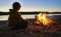 Argentina, Patagonia, Concordia, boy sitting at camp fire at a lake - SSCF00341