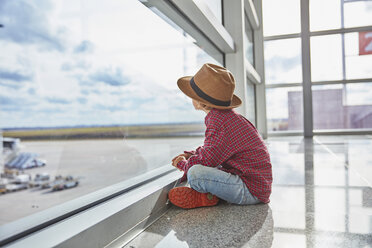 Boy sitting behind windowpane at the airport looking at airfield - SSCF00344