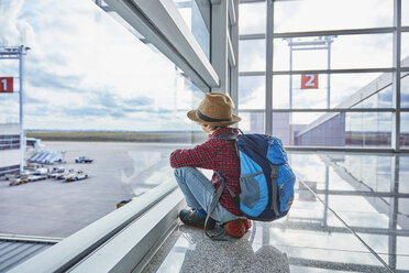 Boy sitting behind windowpane at the airport looking at airfield - SSCF00347