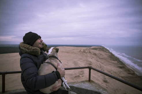 Denmark, North Jutland, Rubjerg Knude Lighthouse, laughing man and his dog at blue hour - REAF00487