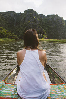 Rear view of woman traveling in boat on river - CAVF59229