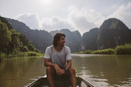 Man looking away while sitting in boat on river against sky - CAVF59232