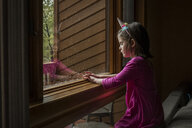 Side view of girl sitting by window at home - CAVF59268