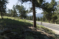 High angle view of man cycling on country road at Estes Park during sunny day - CAVF59274