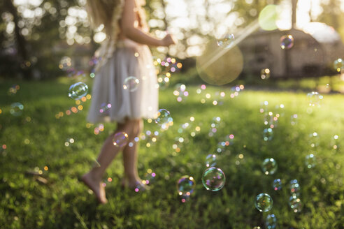 Low section of girl playing with bubbles on grassy field at park - CAVF59301