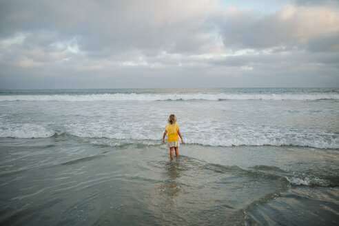 High angle view of carefree girl standing in sea at beach against cloudy sky - CAVF59310