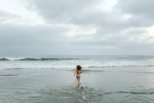 Rear view of shirtless girl running towards sea against cloudy sky at beach - CAVF59316