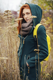 Portrait of teenage girl with backpack standing amidst plants - CAVF59331