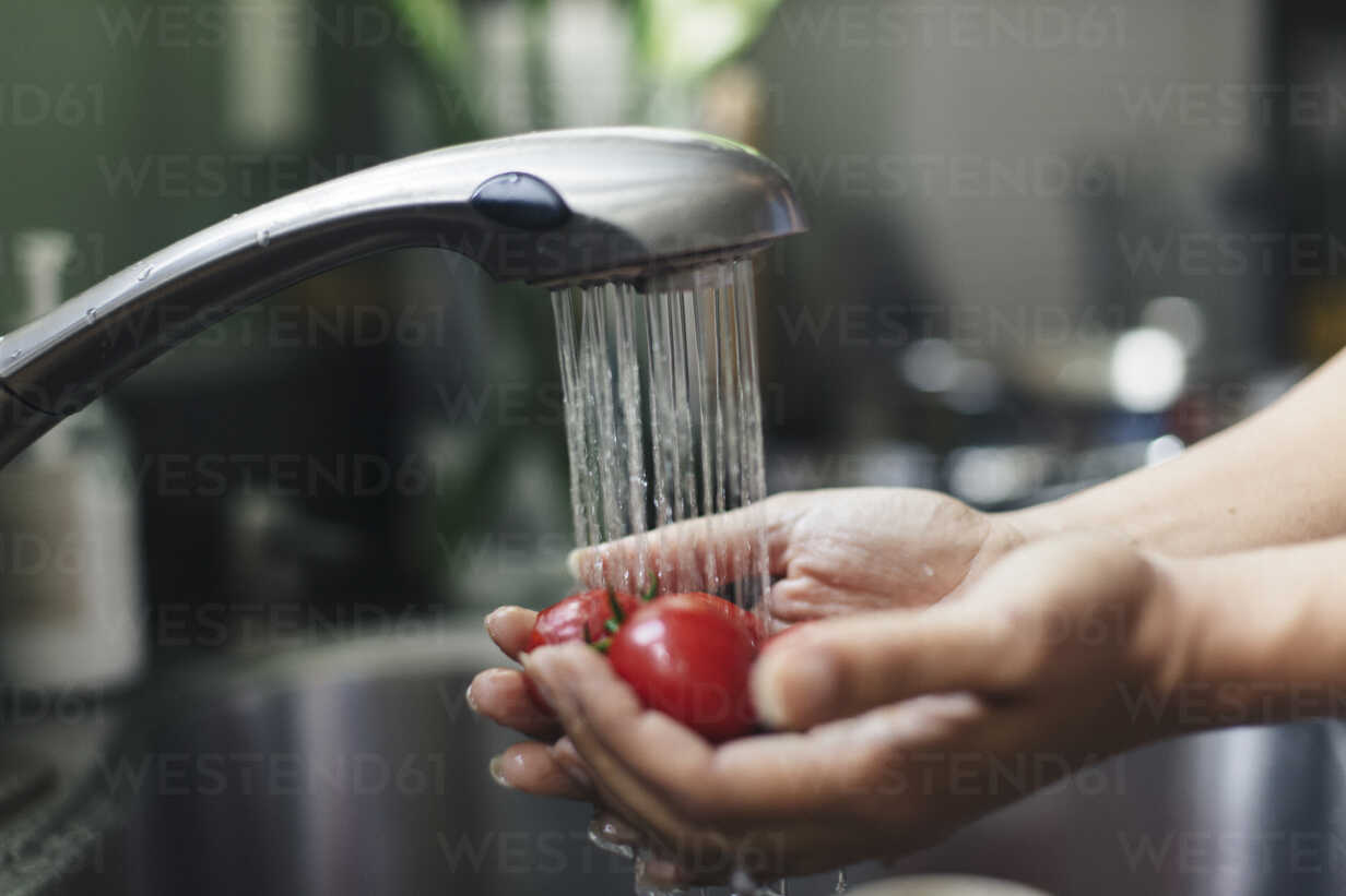 Cropped Hands Of Woman Washing Cherry Tomatoes Under Running Water In Kitchen Sink Cavf59355 Cavan Images